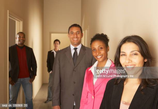 Portrait of five business executives standing and smiling