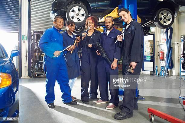 Portrait of five college students beneath car in garage workshop