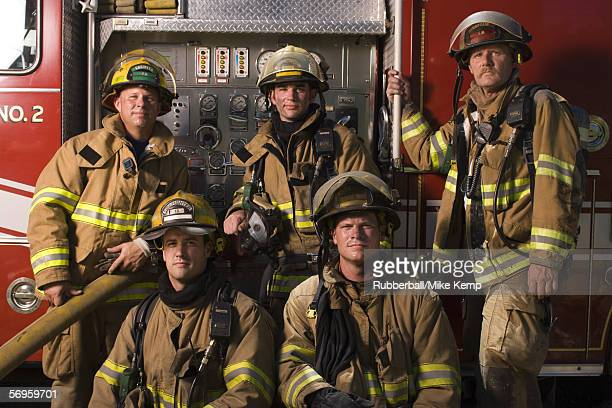Portrait of five firefighters standing in front of a fire engine