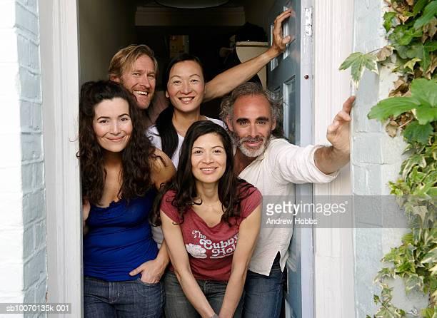 Portrait of five friends in doorway of house