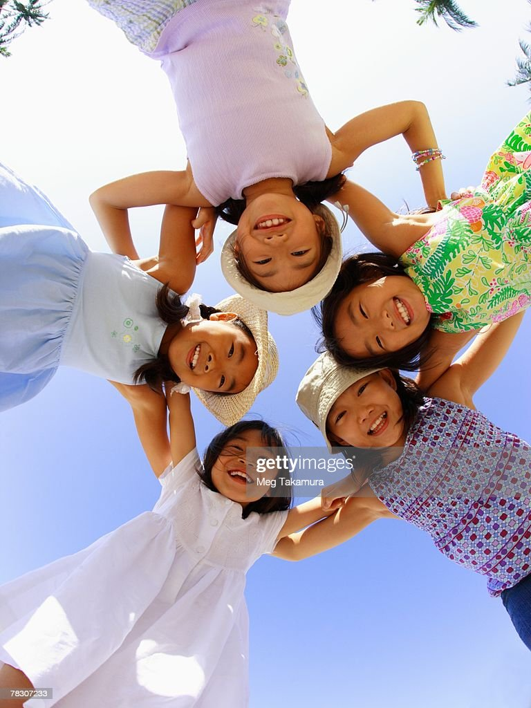 Portrait of five girls standing in a huddle and smiling : Stock Photo