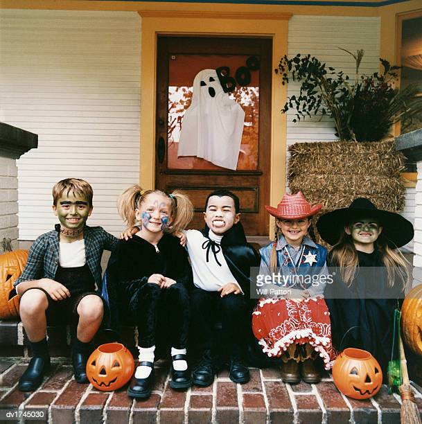 Portrait of Five Young Boys and Girls in Halloween Costumes Sitting on a Front Door Step