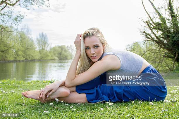Portrait of flexible young woman exercising near lake