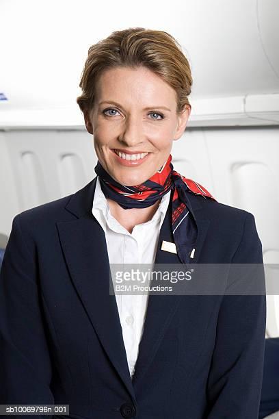 portrait of flight attendant standing in aisle of aeroplane - ネッカチーフ ストックフォトと画像