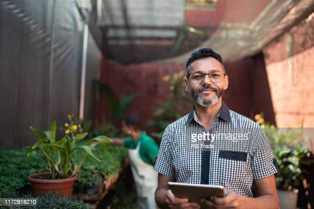 portrait of florist using tablet at small business flower shop - business owner stock pictures, royalty-free photos & images