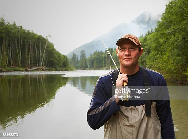 Portrait of fly fisherman standing in river