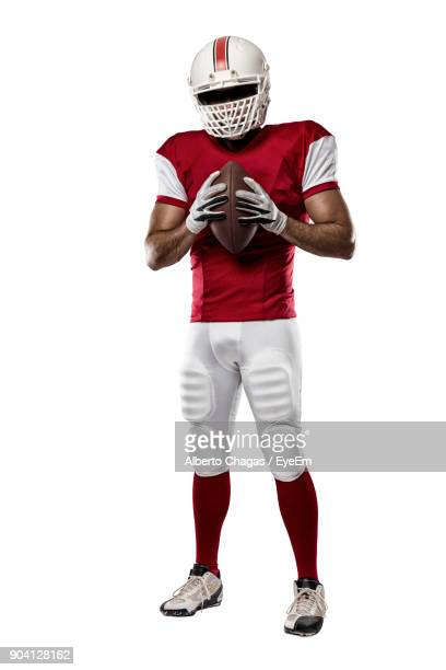 Portrait Of Football Player In Uniform Standing Against White Background