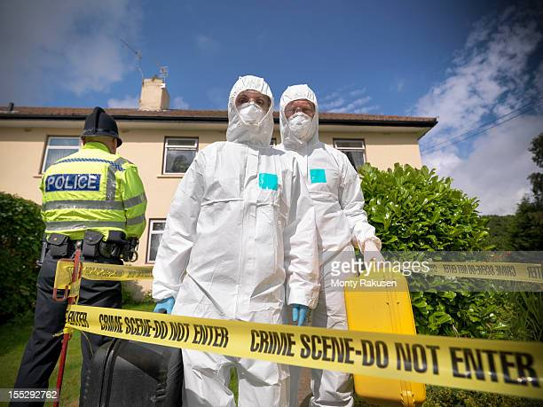 Portrait of forensic scientists in front of police tape and house at crime scene, policeman in background