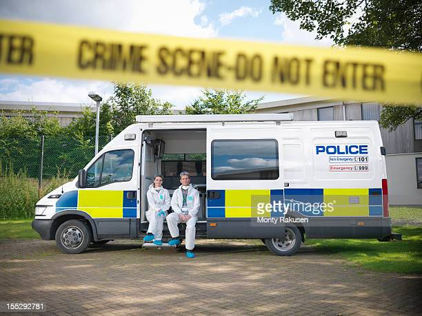 portrait of forensic scientists sitting in police incident van at crime scene - cordon tape stock pictures, royalty-free photos & images