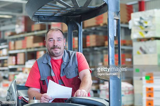 Portrait of forklift truck driver in hardware store warehouse