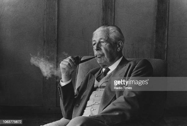 Portrait of former British Prime Minister Harold Macmillan sitting in an armchair while smoking his pipe circa 1975