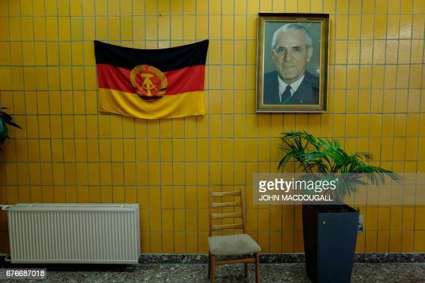 A portrait of former east German leader Willi Stoph hangs next to a GDR flag in a recreated east German party hall for a 'Socialist revival live...