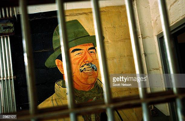A portrait of former Iraqi leader Saddam Hussein is seen behind the bars of an office within the former Abu Ghraib prison which is being cleaned and...