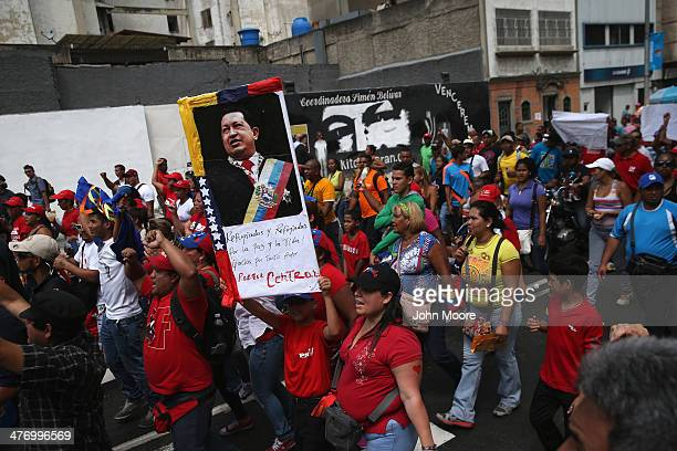 A portrait of former Venezuelan President Hugo Chavez looks on as government supporters march on March 6 2014 in Caracas Venezuela Progovernment...