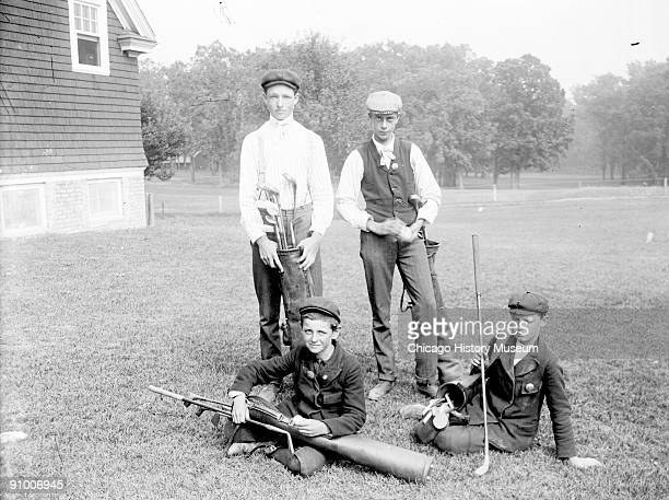 Portrait of four caddies two boys sitting and two boys standing on the grounds of the golf course at the Midlothian Country Club in Midlothian...