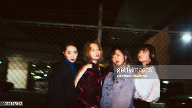 Portrait of four contemporary young Japanese woman at night street.
