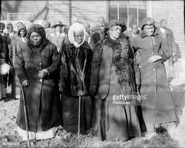 Portrait of four former slaves from left unidentified Anna Angales Elizabeth Berkeley and Sadie Thompson as they pose together at a gathering...
