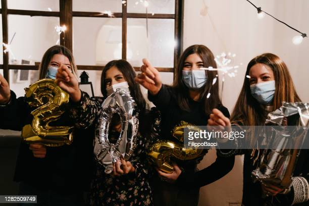 portrait of four friends celebrating 2021 new year's eve together - new year's eve stock pictures, royalty-free photos & images