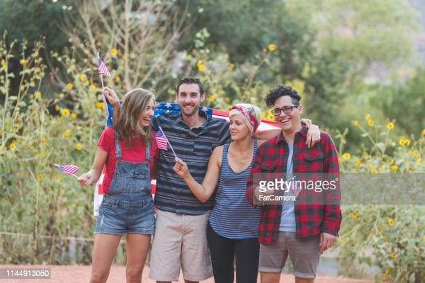 portrait of four friends holding up american flags - political party stock pictures, royalty-free photos & images