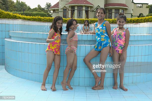 portrait of four girls standing in an empty swimming pool - indian bikini stock pictures, royalty-free photos & images