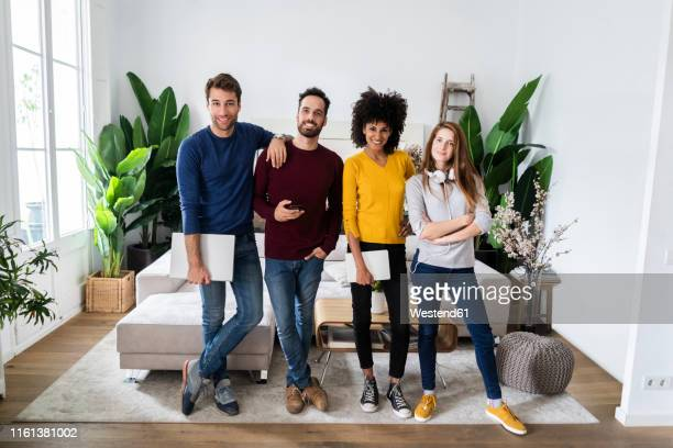 portrait of four happy friends standing side by side in living room - 25 29 anni foto e immagini stock
