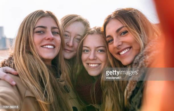 Portrait of four happy friends taking selfie