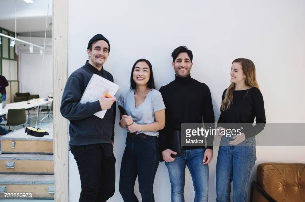 portrait of four happy people in creative office - side by side stock photos and pictures
