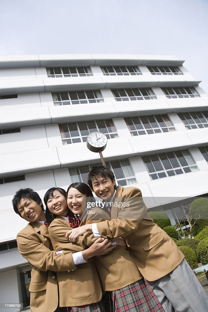 Portrait of four high school students embracing each other, smiling and looking at camera : Photo