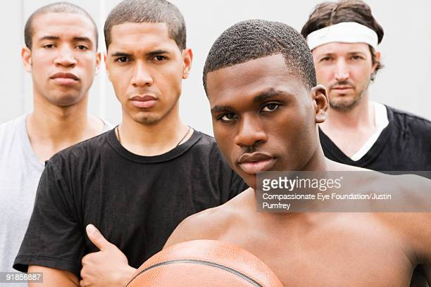 portrait of four men with basketball