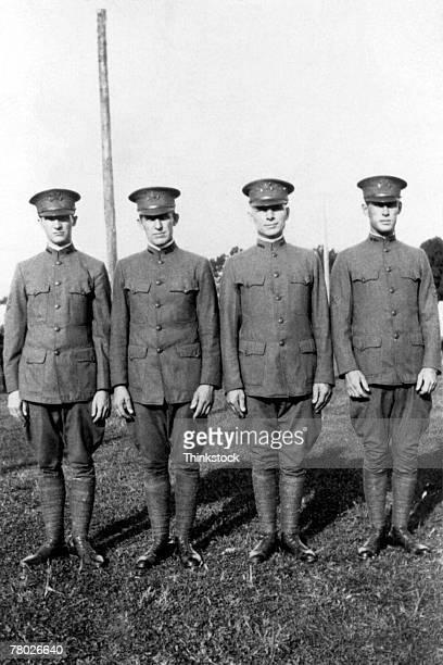 portrait of four military men in uniform standing outdoors in a line; circa ww1. - thinkstock foto e immagini stock