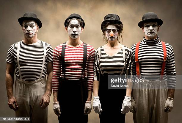 Portrait of four mimes standing in row