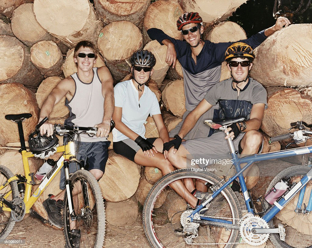 Portrait of Four People Sitting on Logs With Their Mountain Bikes : Stock Photo