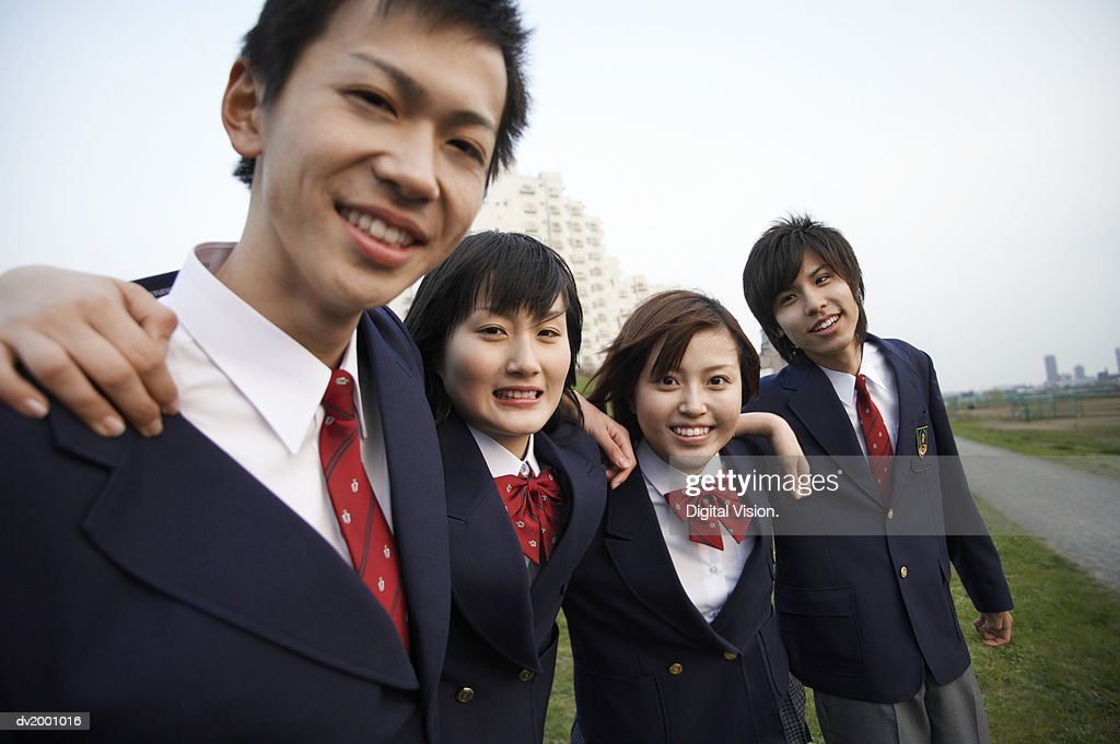 Portrait of Four School Friends Standing on the Grass With Their Arms Around Each Other : Stock Photo