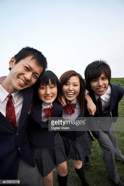 Portrait of Four School Friends Standing on the Grass With Their Arms Around Each Other