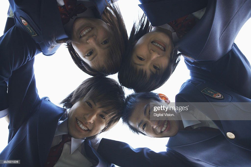 Portrait of Four School Friends With Their Arms Around Each Other From Below : Stock Photo