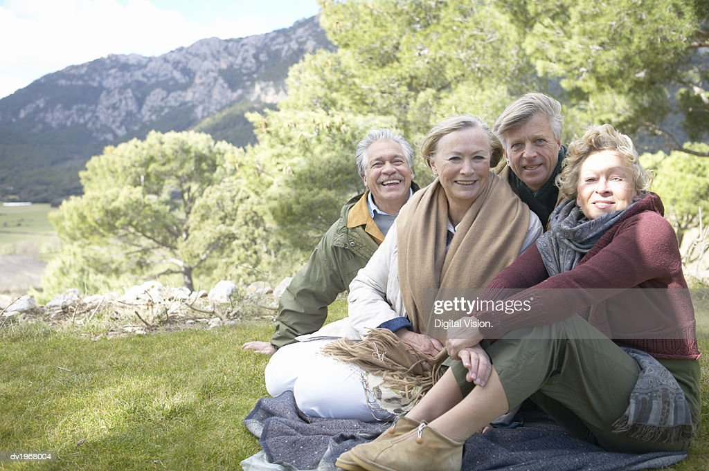 Portrait of Four Senior Men and Women Sitting on a Rug in the Countryside : Stock Photo