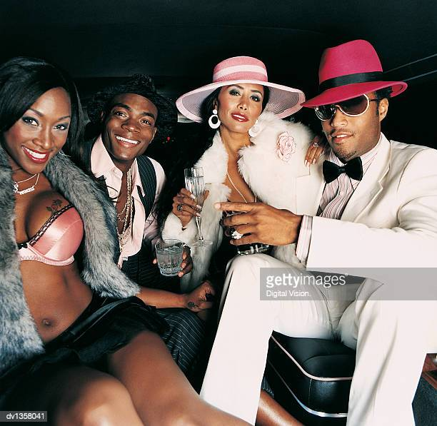 portrait of four smiling, young adults sitting in the back seat of a limousine - dress hat stock pictures, royalty-free photos & images