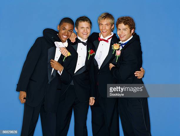 portrait of four teenage boys standing with their arms around each other