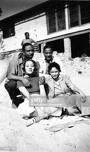 Portrait of four unidentified people as they pose on the beach outside the Idlewild Club House Idlewild Michigan September 1938 Idlewild known as...