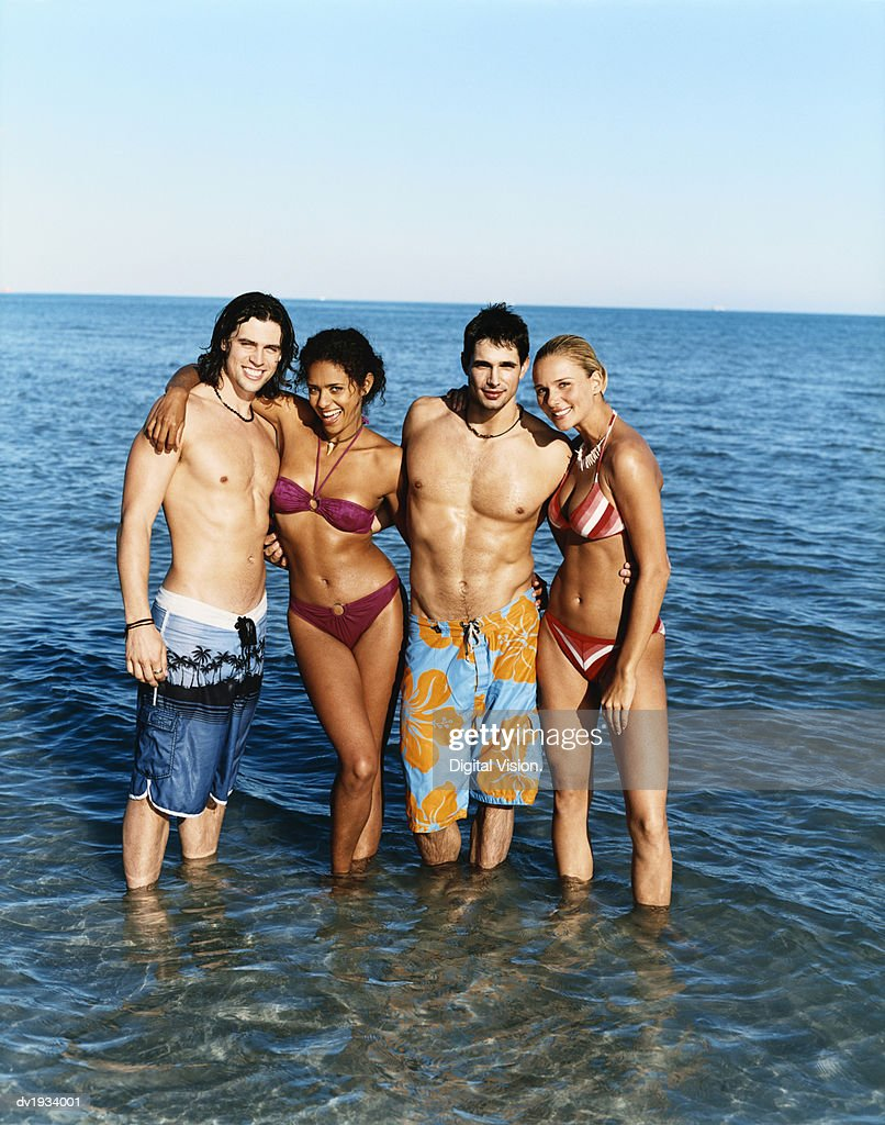 Portrait of Four Young Adults Standing in the Sea in a Line : Stock Photo