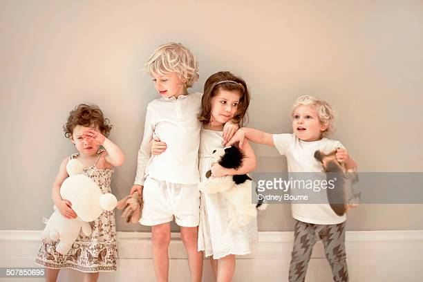 portrait of four young children in a row, one crying - sibling stock pictures, royalty-free photos & images