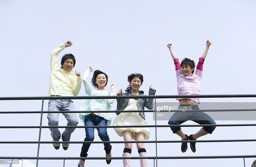 Portrait of four young people jumping behind the railing, low angle view, blue background, Japan : Photo