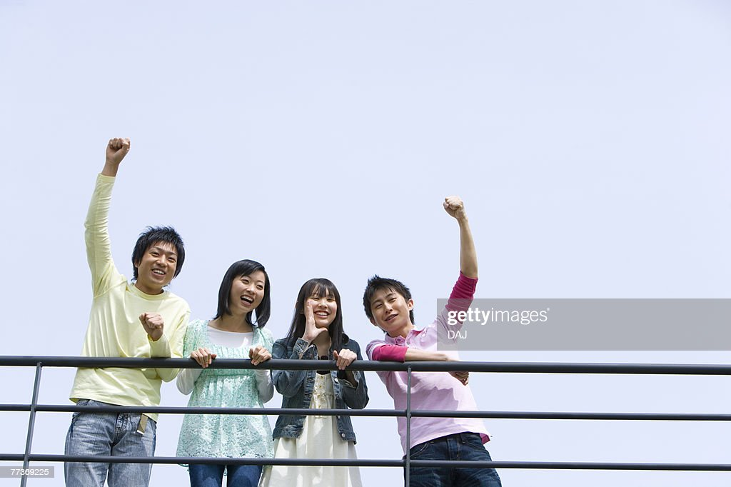 Portrait of four young people, men punching air, low angle view, blue background, copy space, Japan : Photo