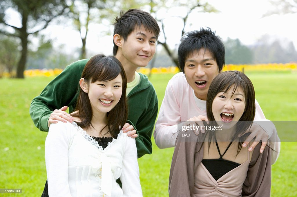 Portrait of four young people on lawn, smiling and looking at camera, front view, Japan : Photo