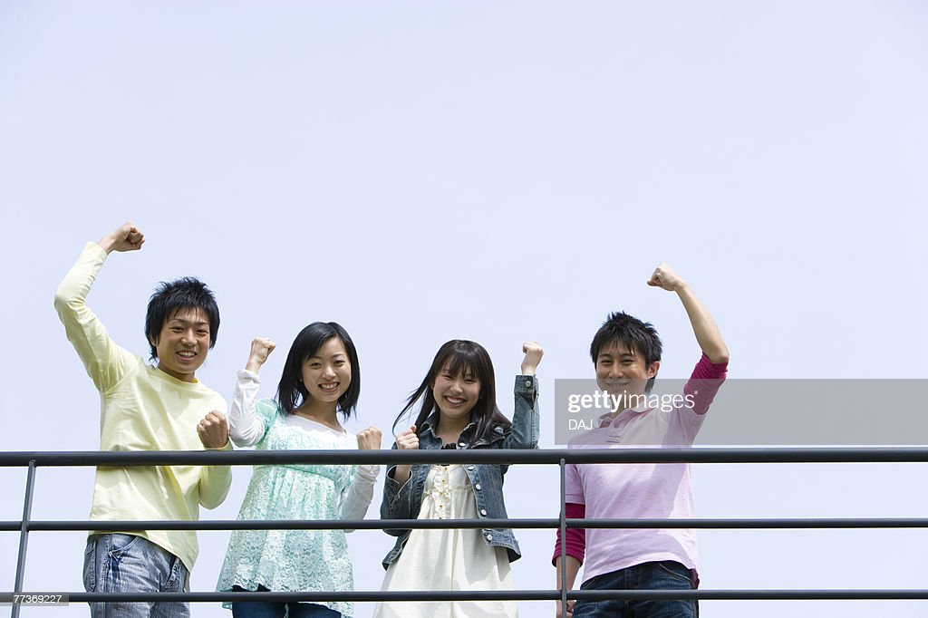 Portrait of four young people punching air behind the railing, low angle view, blue background, copy space, Japan : Photo