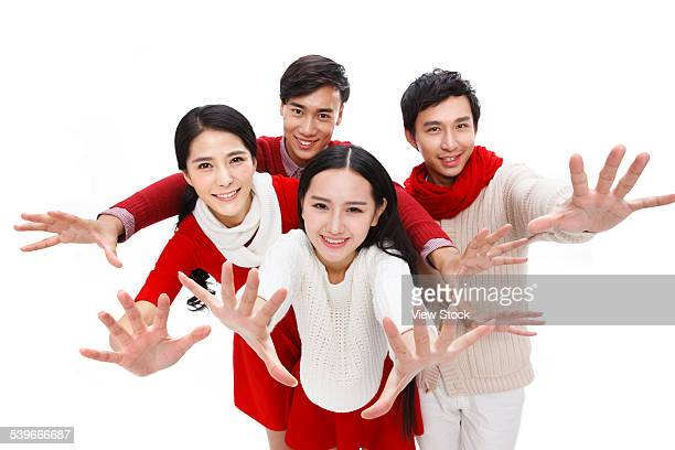 Portrait of four young people with arm outstretched