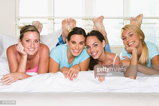 Portrait of four young women lying down side by side on a bed