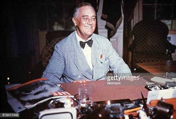 Portrait of Franklin Delano Roosevelt seated at his desk smiling Undated color slide