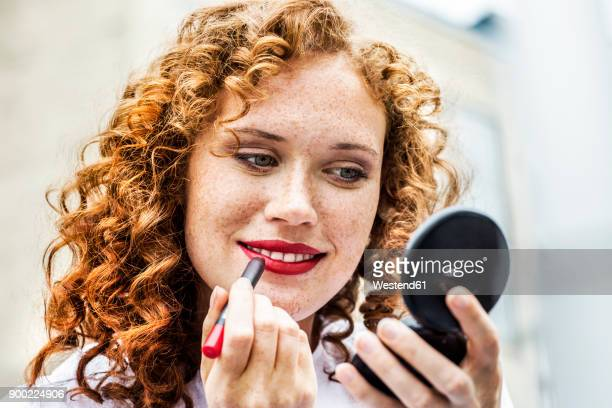 portrait of freckled young woman applying lipstick - lippenstift stock-fotos und bilder