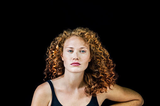 Portrait of freckled young woman with curly red hair in front of black background - gettyimageskorea